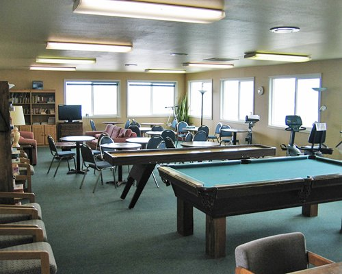 An indoor pool table library with television and fitness area.