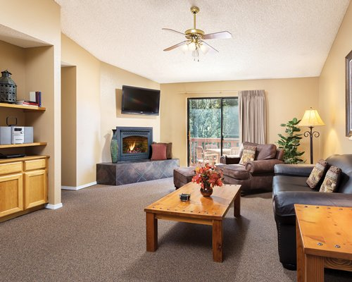 A well furnished living room with sleeper sofa television and a fire in the fireplace.