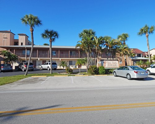 Scenic exterior view of Sea Oats Beach Club Resort with car parking.