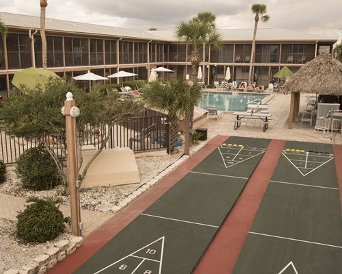 A scenic view of two shuffleboards alongside multi story resort units.