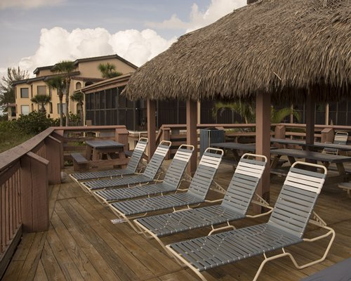A view of chaise lounge chairs alongside thatched sunshades.