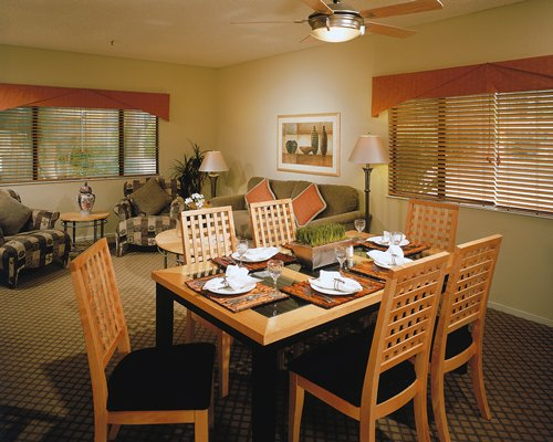 A well furnished living area alongside a dining table.