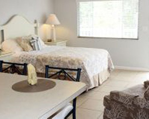 A well furnished bedroom with a king bed alongside a dining area and kitchen.