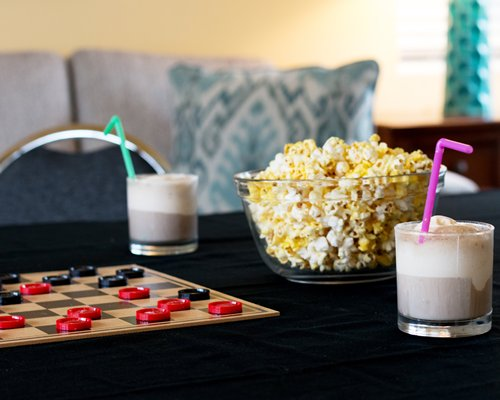 An indoor table with checkers popcorn and milkshakes.