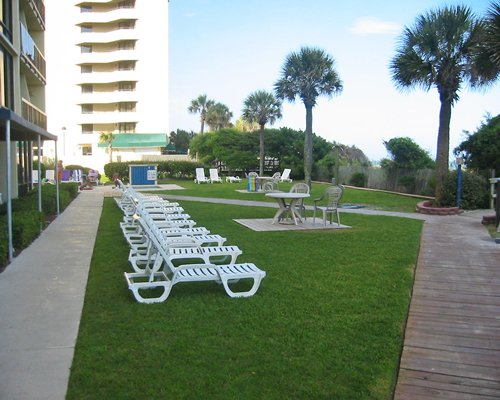 A view of chaise lounge chairs alongside resort units.