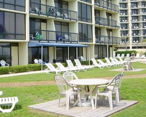 Scenic view of multiple unit balconies with picnic area and chaise lounge chairs and patio table.