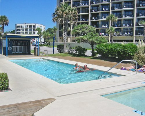Scenic view of multiple unit balconies alongside outdoor swimming pool and hot tub.