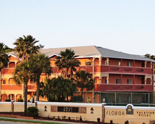 Exterior view of multiple unit balconies at Florida Vacation Villas with palm trees.