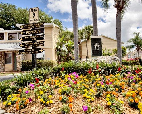 A street signboard in resort alongside flowering shrubs.