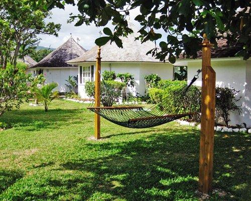 A hammock in a landscape alongside multiple units of the resort.