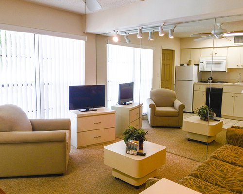 A well furnished living room with open plan kitchen and television.