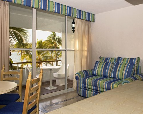 A well furnished bedroom with couch dining area and balcony with patio furniture.