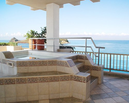 Outdoor hot tub with balcony and ocean view.