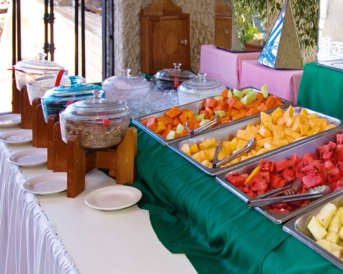A buffet with sliced fruits.