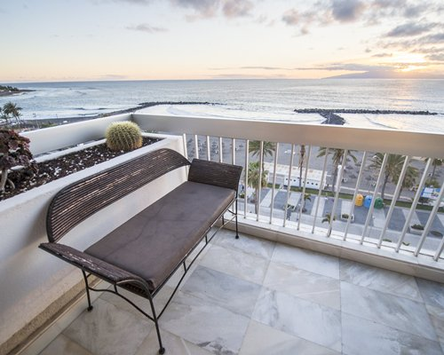 Balcony with a bench and ocean view.