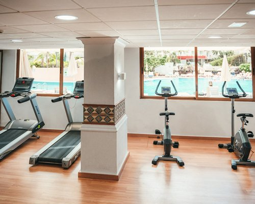 A well equipped indoor fitness center with the view of swimming pool.