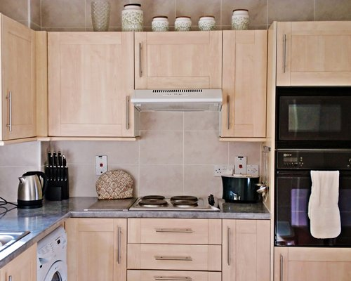 A well equipped modular kitchen with a microwave oven.