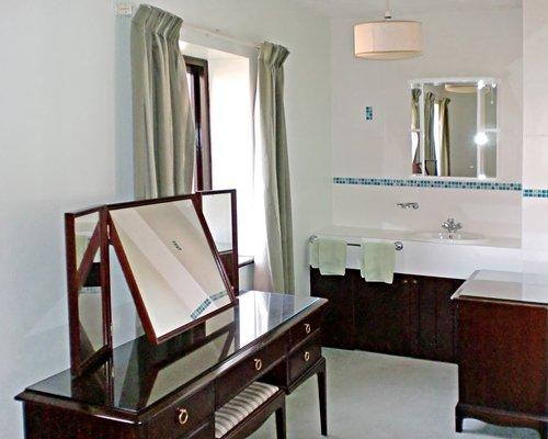 A bathroom with a single sink vanity and a dressing table.