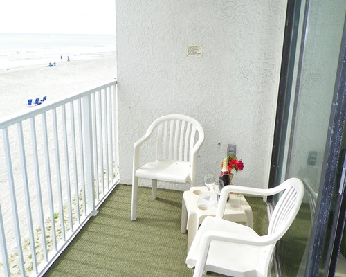 Balcony with patio furniture facing the beach.