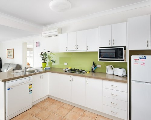 A well equipped modular kitchen with a microwave and refrigerator.