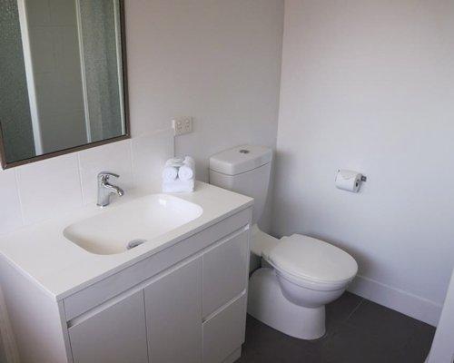 A bathroom with single sink vanity enclosed toilet.