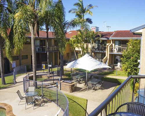 Scenic view of multiple unit balconies and picnic area with barbecue stove.