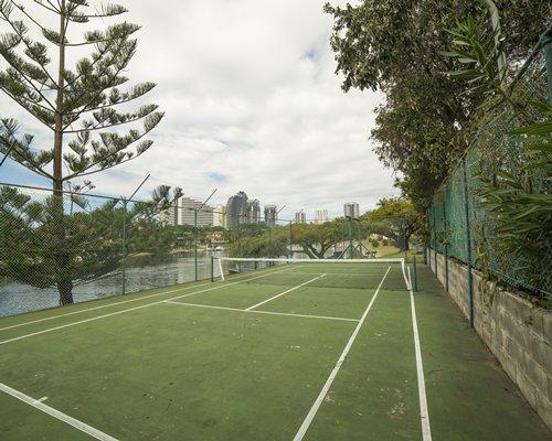 An outdoor tennis court alongside water view.