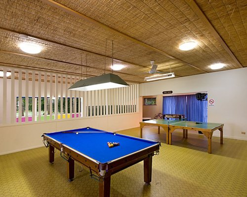 An indoor play area with pool table and tennis table.