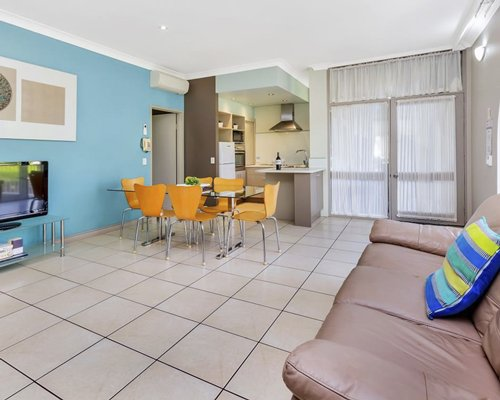 A well furnished living room with open plan dining area kitchen television and outdoor view.