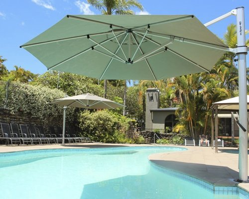 An outdoor swimming pool with cantilever umbrellas.