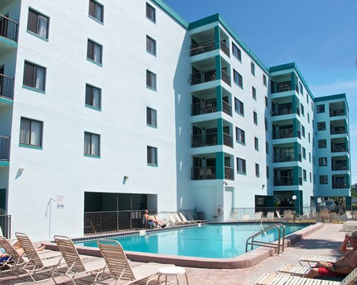 View of multiple unit balconies with outdoor swimming pool and chaise lounge chairs.