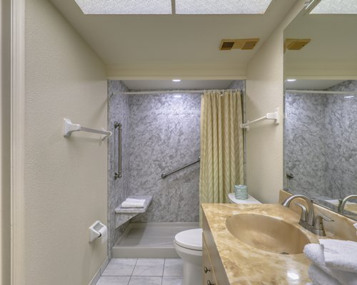 A bathroom with bath tub shower and single sink vanity.