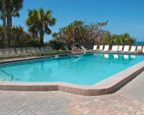 View of thatched sunshade with patio chairs alongside barbecue grill.