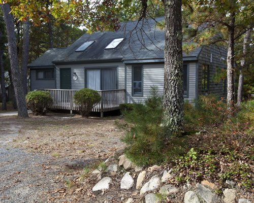 An exterior view of a Cape Cod Holiday Estates resort unit surrounded by wooded area.