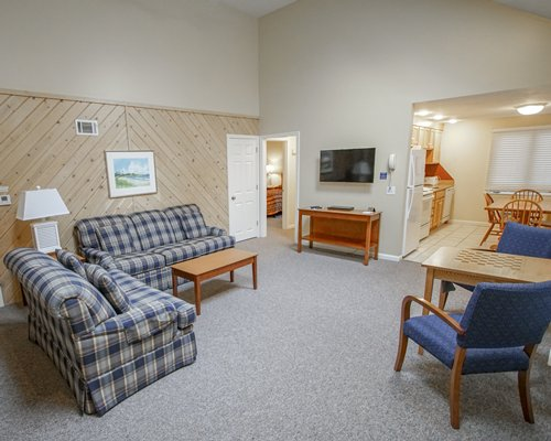 A well furnished living area with a television and a chess table.