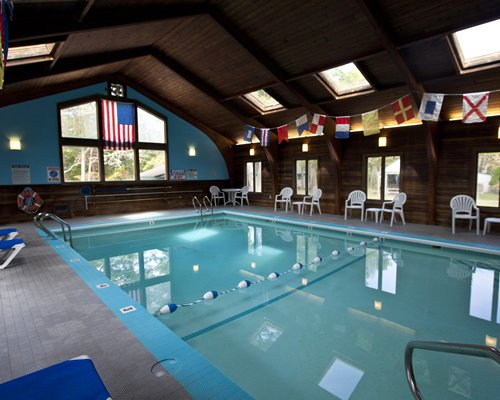 A large indoor swimming pool with patio chairs.