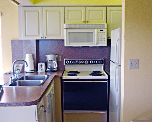 A well equipped modular kitchen with a microwave.