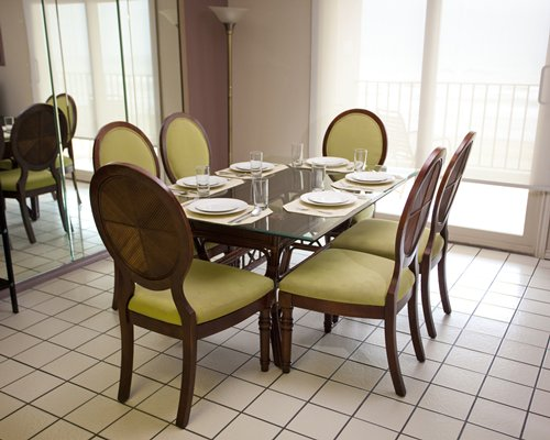 A well furnished dining area with a glass top table.