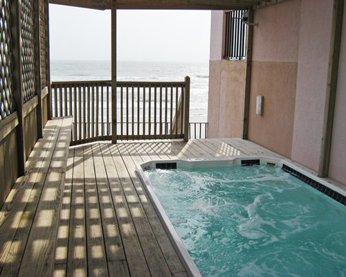 A hot tub in a balcony facing the ocean.
