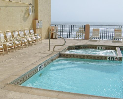 An outdoor swimming pool and hot tub with chaise lounge chairs along the shore.