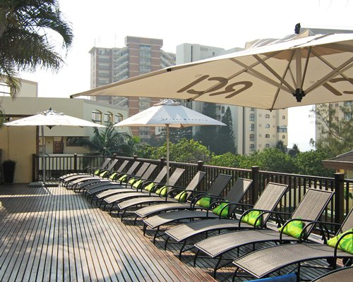 An outdoor chaise lounge chairs with cantilever umbrella.