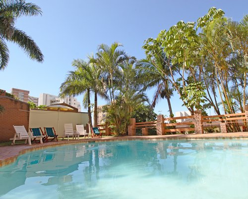 An outdoor swimming pool with chaise lounge chairs alongside palm trees.