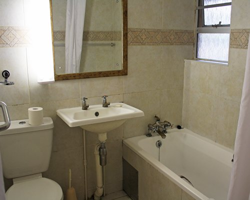 A bathroom with bath tub and shower with single sink vanity.