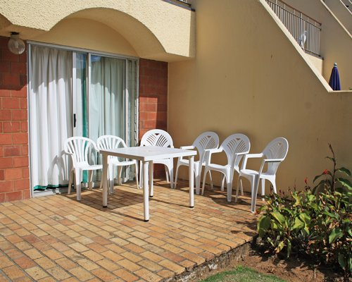 An outside view of resort unit with patio furniture.
