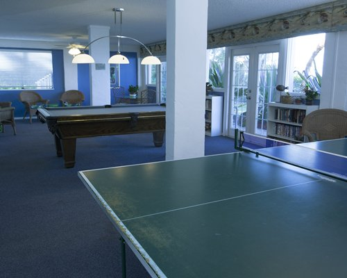 Indoor recreational room with ping pong and pool tables.