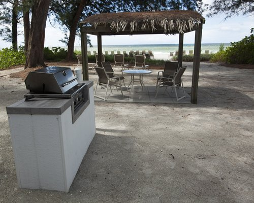 An outdoor barbecue grill with thatched sunshades.