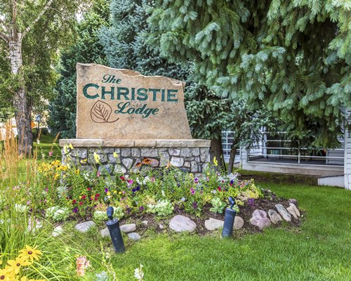 Ground view of The Christie Lodge with flowering shrubs.