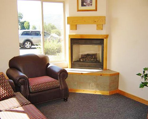 A well furnished living room with sofa and fireplace with an outside view.