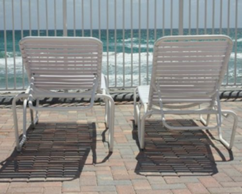 A view of chaise lounge chairs alongside the ocean.
