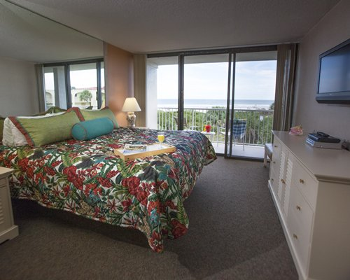 A well furnished bedroom with king bed and balcony with patio chairs and ocean view.